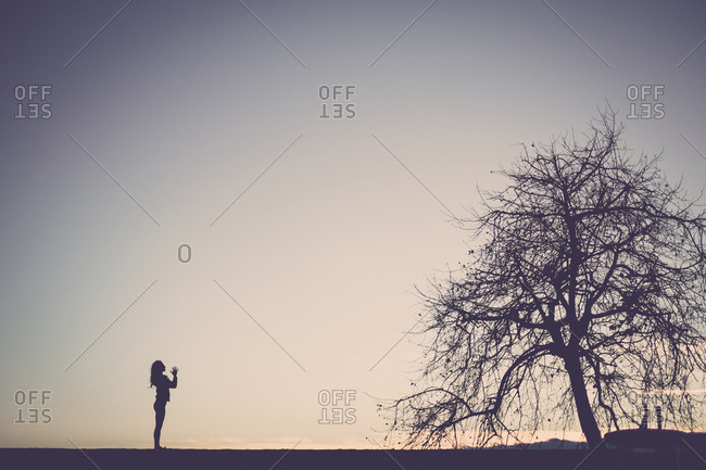 Silhouette of a woman practicing yoga in nature