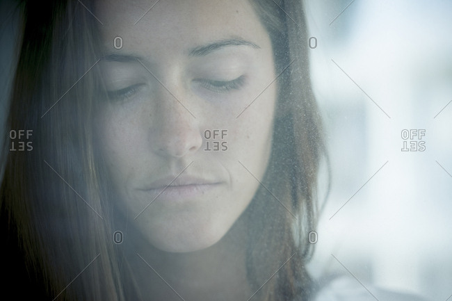 Portrait of pensive young woman behind windowpane