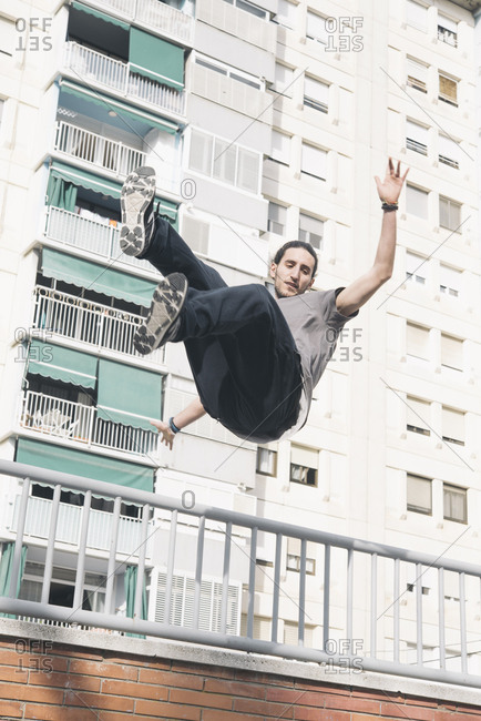 Young man doing Parkour in the city jumping in the air