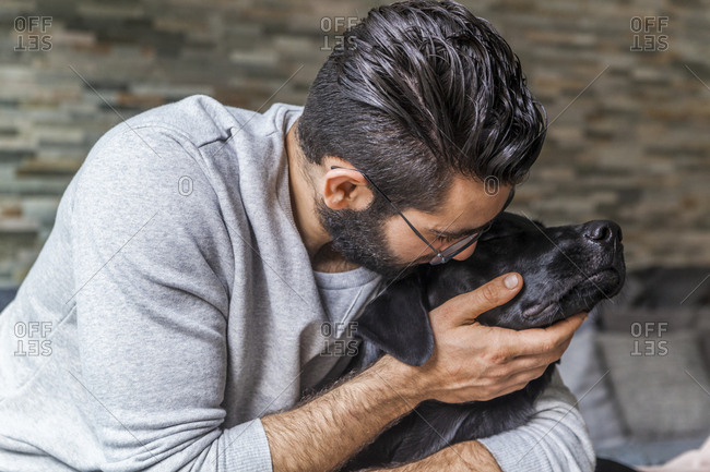 Man cuddling with his dog at home