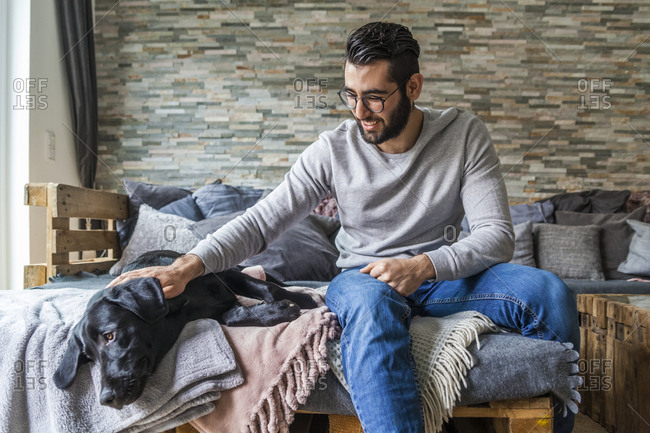 Man stroking his dog on the couch at home