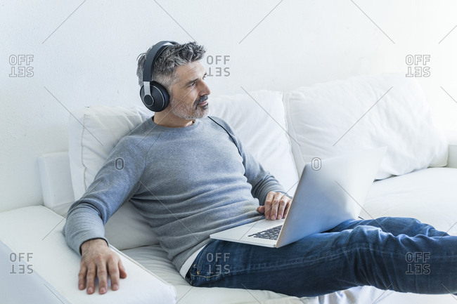 Mature man at home using laptop and wearing headphones