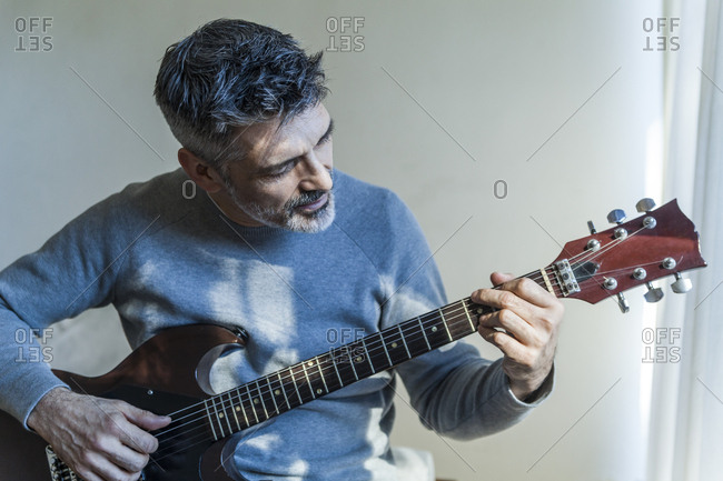 Mature man at home playing electric guitar