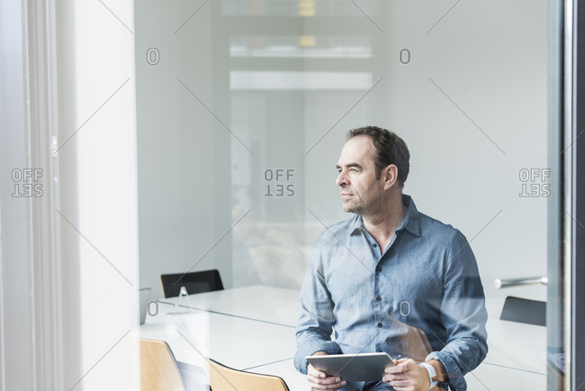 Businessman with tablet looking sideways in office