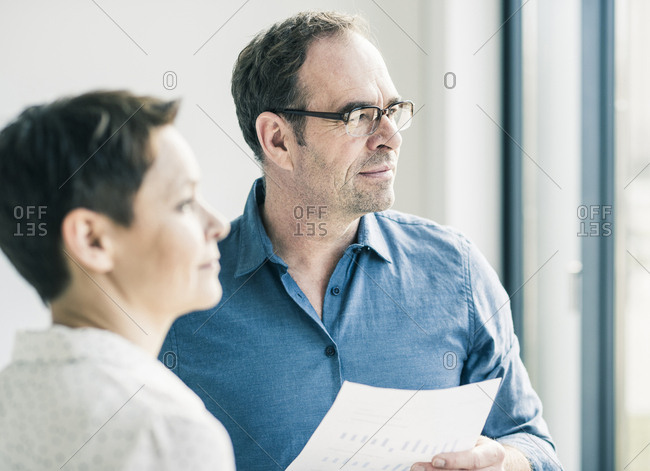 Businessman and businesswoman looking out of window