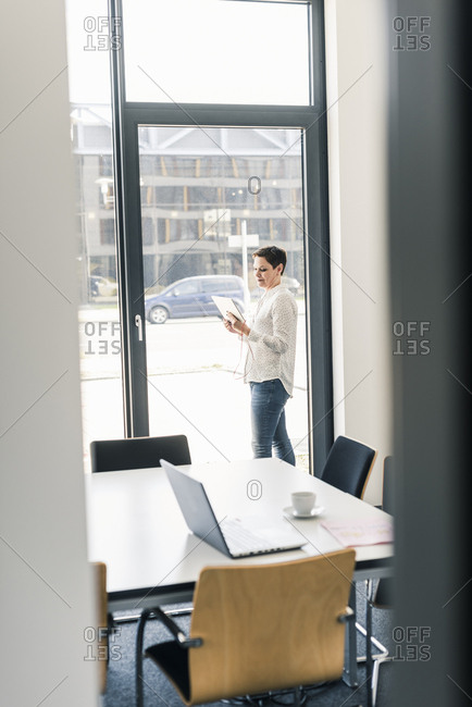 Businesswoman using tablet at the window