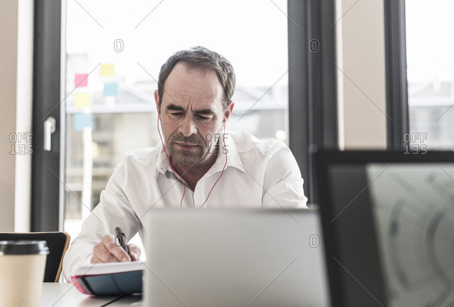 Businessman with earbuds working at desk in office
