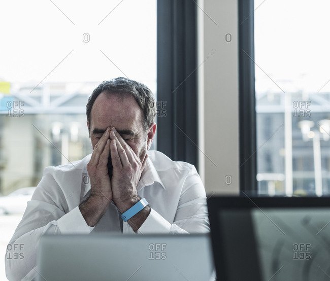 Exhausted businessman sitting at desk in office