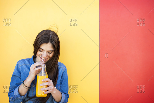 Smiling young woman in front of colorful wall drinking orange juice