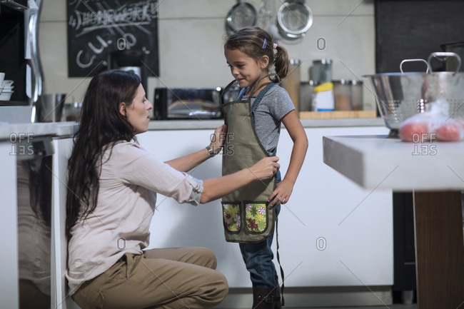 Mother tying apron for daughter in kitchen