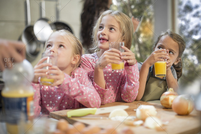Girls drinking juice in kitchen looking up