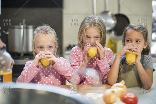 Girls drinking juice in kitchen