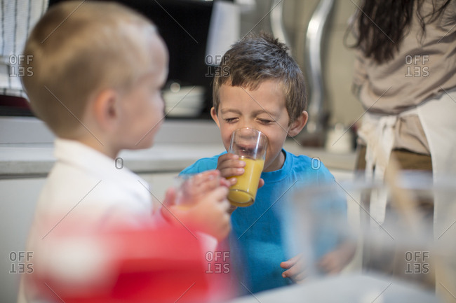 Two boys drinking juice in kitchen