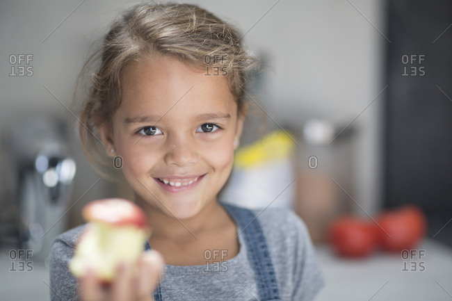 Portrait of smiling girl with apple in kitchen