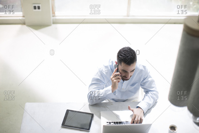 Young businessman working in office - using mobile devices