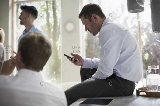 Businessman using smart phone in a meeting