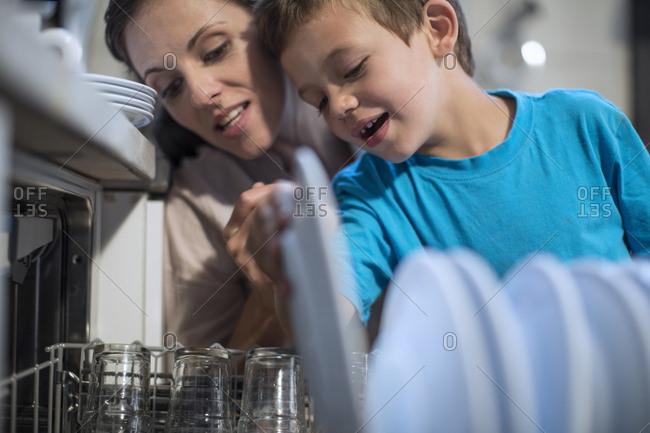 Boy packing plates into dishwasher