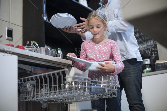 Daughter packing plates into dishwasher