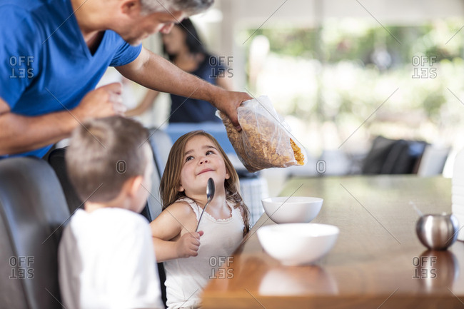 Father preparing cereal breakfast with kids