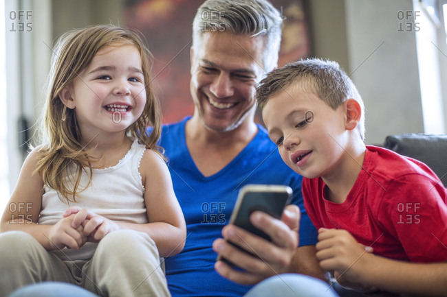 Happy father with children sharing cell phone