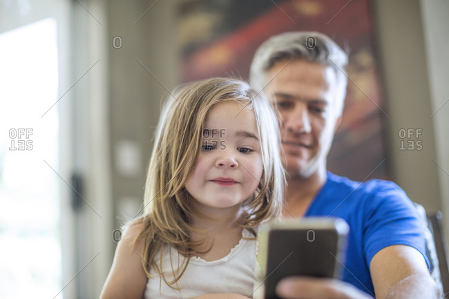Father and daughter sharing cell phone