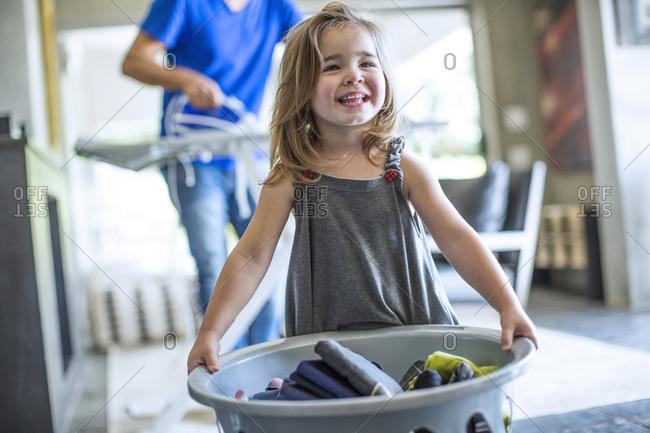 Happy baby girl holding laundry basket