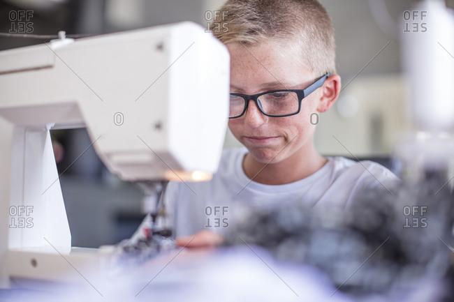 Boy wearing glasses working on sewing machine