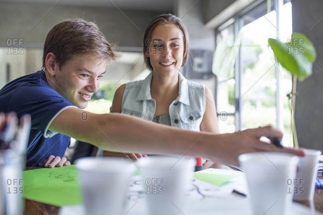 Boy and girl examining plant