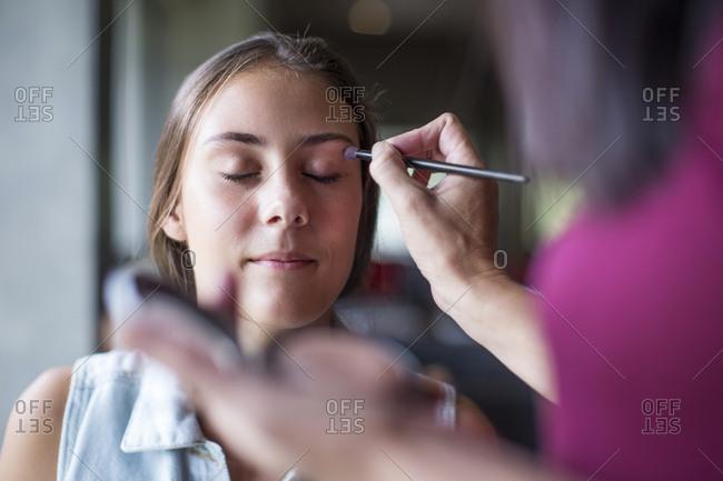 Mother helping daughter applying make up