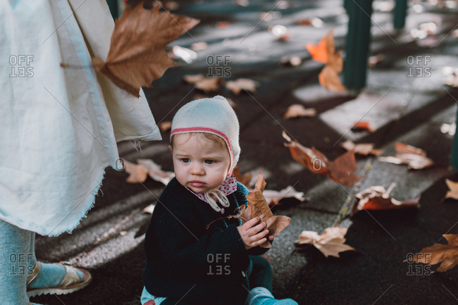 Baby playing in the fallen leaves during Autumn