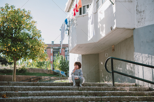 Young girl sitting on cement stairs