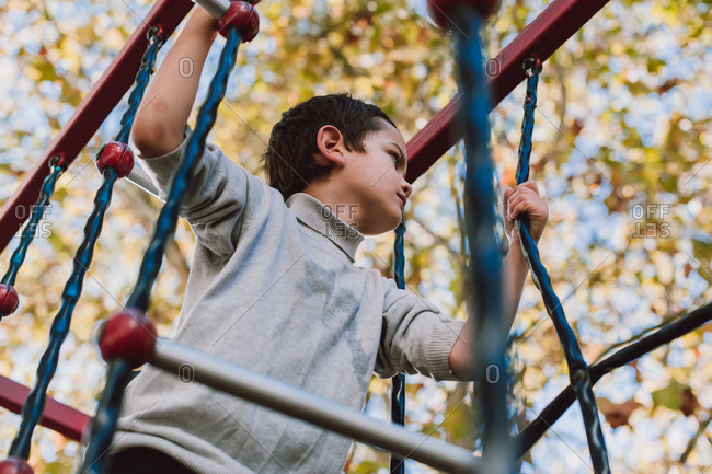 Young boy playing on the monkey bars