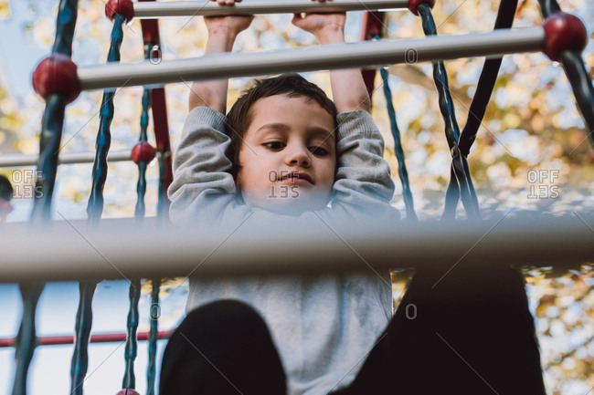 Young boy swinging on the monkey bars