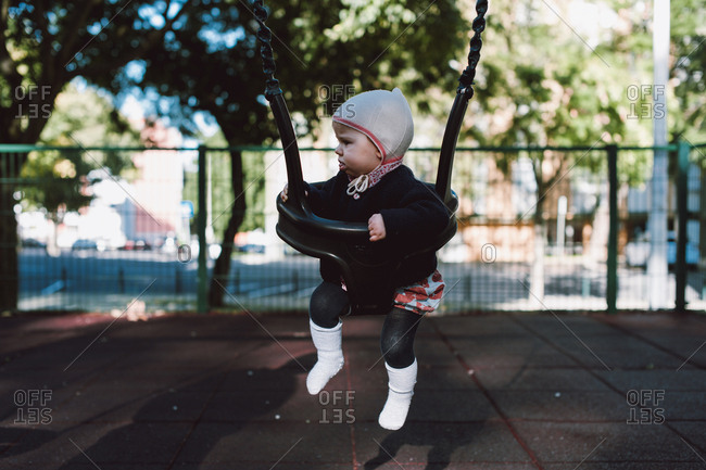 Baby on a swing set at the playground