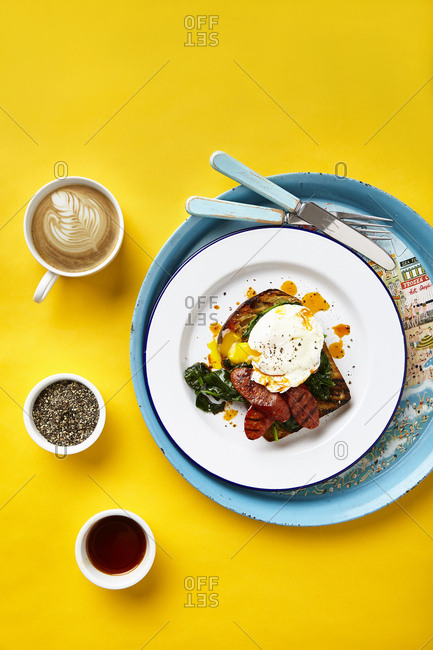 Poached egg on toast with spinach, fried chorizo and paprika oil on yellow surface and large round graphic serving tray.