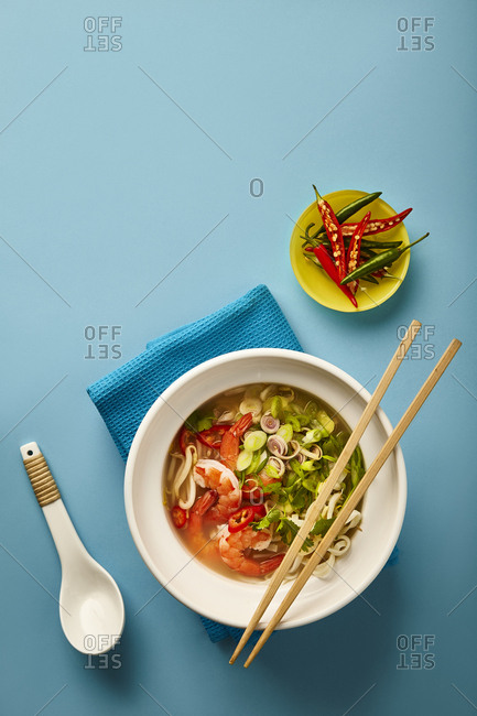 Prawn and vegetable Pho with wooden chop sticks and side fresh chili. Photographed on turquoise background.