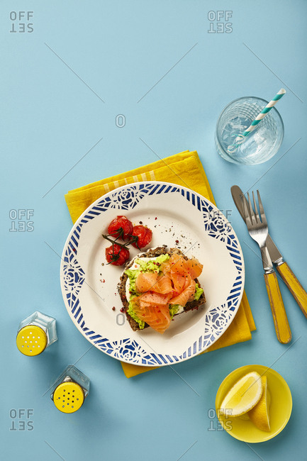 Salmon and Avocado on toasted rye bread and roasted side tomatoes. Photographed on turquoise background.