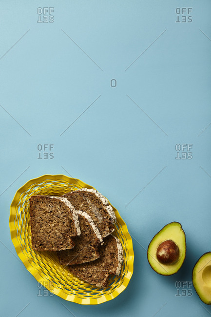 Rye bread in yellow basket and open avocado on turquoise surface