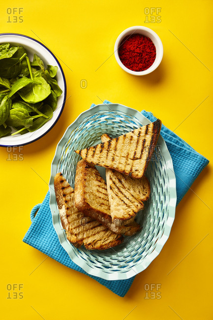 Grilled white bread with fresh spinach and paprika served in blue bread basket on yellow surface.