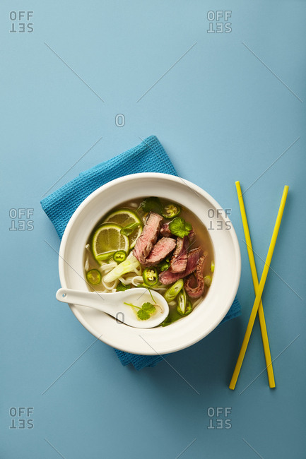 Beef Vegetable Pho. Photographed on turquoise background with yellow chopsticks