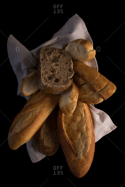 The different types of breads in the basket are lined with coarse cloth