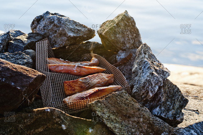 Grilled meat in metal net on stones by sea
