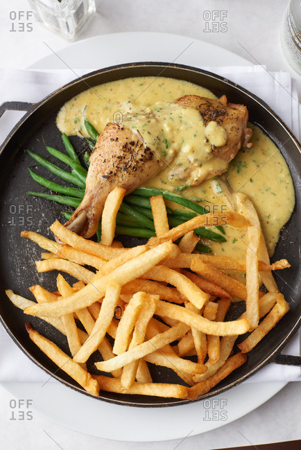 Chicken Confit with frites and green beans with mustard sauce served in a French restaurant.