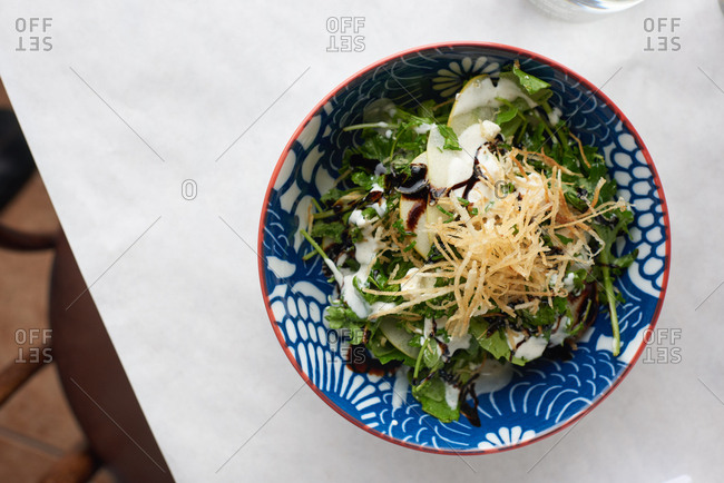 Kale Salad with fried thin croutons and apple served with balsamic and creamy dressing served in a French restaurant.