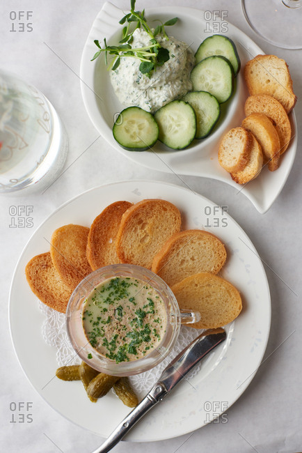 Homemade Pate and homemade boursin cheese served with crostini and cucumber on a white tablecloth at a French Restaurant.
