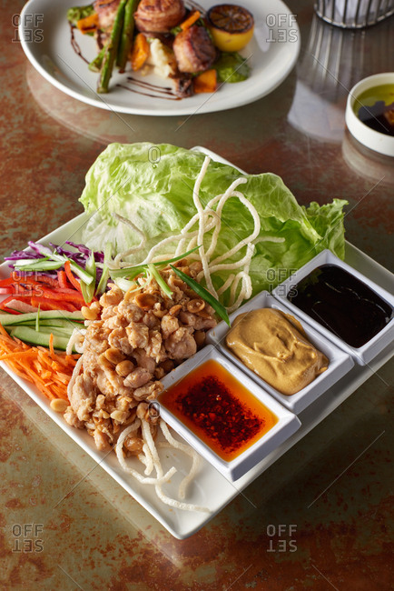 All the pieces for chicken lettuce wraps including sauteed chicken, lettuce, red pepper, carrots, cucumber and cabbage