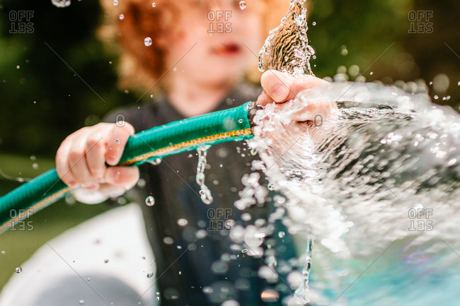 Child playing with garden hose in pool