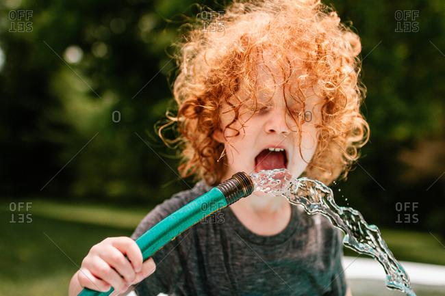 Child drinking from garden hose