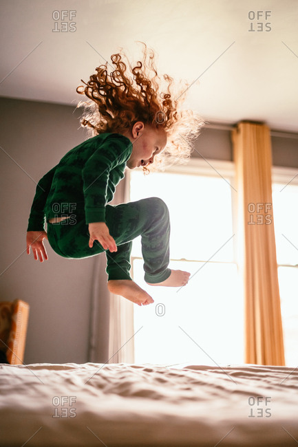 Red haired boy jumping on bed