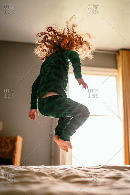 Child with curly red hair jumping on bed